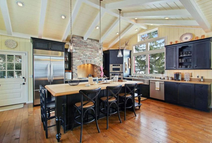 Kitchen with black cabinets with beadboard doors, vaulted ceiling, large island and wood countertop