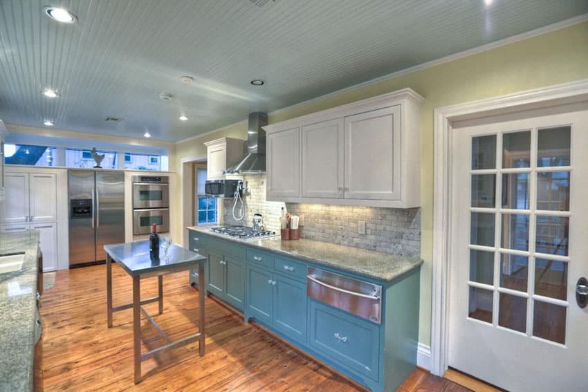 Kitchen with blue bottom cabinets and white upper cabinets with portable metal island
