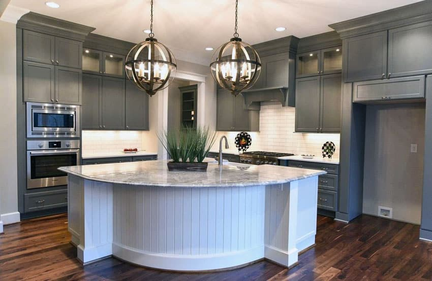 Kitchen with gray cabinets, white island with white subway tile