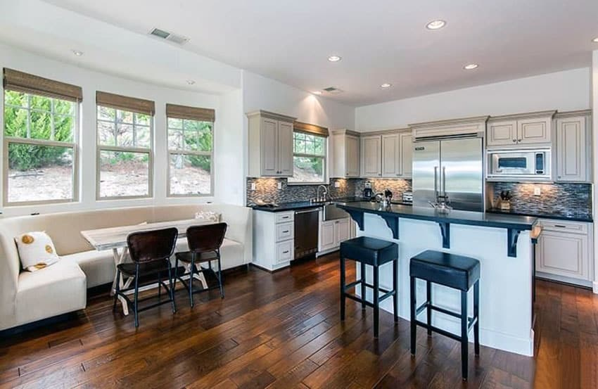 Kitchen with window seat and wood table with black counter breakfast bar