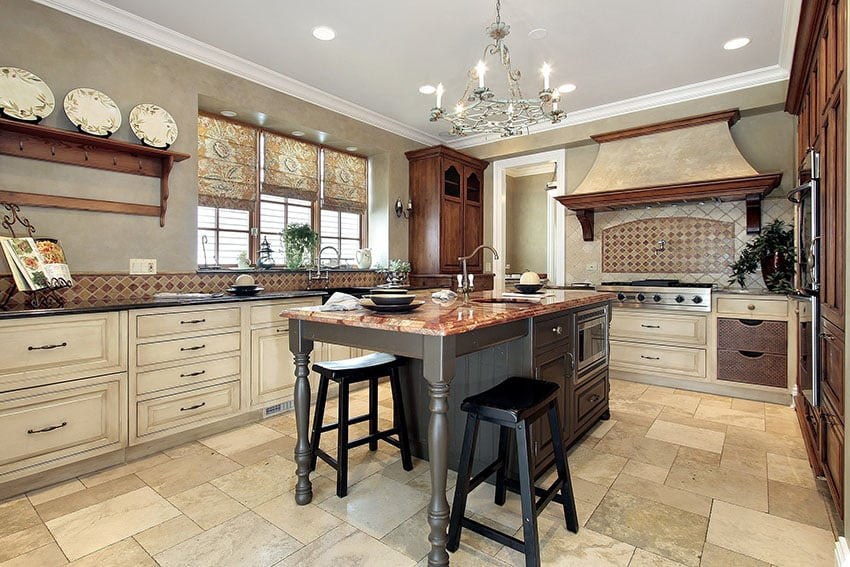 Luxury kitchen with cream color antique style cabinets and dark wood island