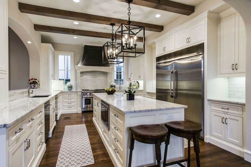 Luxury kitchen with white cabinets, oak wood floors, arabescato statuary marble counters and black wrought iron lamps