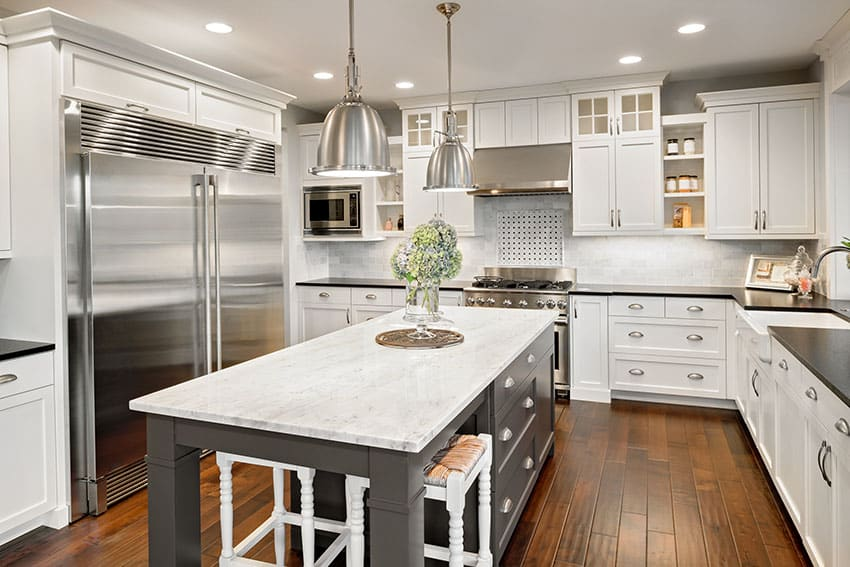 Luxury white cabinet kitchen with gray island, black counter and wood floors