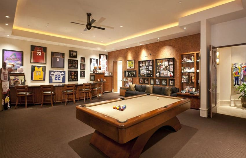 Man cave with wood bar, sports jerseys, sports decor and pool table