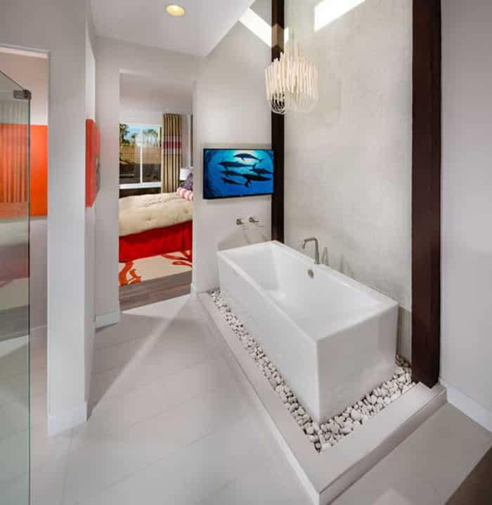 Minimalist modern master bathroom with elevated tub on white rocks