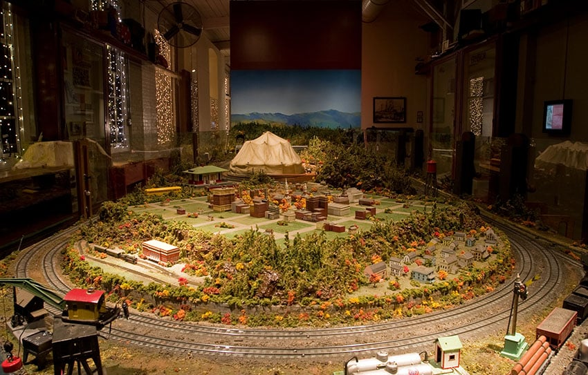Model train room with forest and town landscape