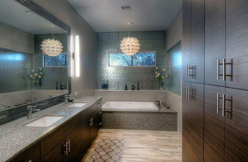 Modern bathroom with brown vanities and pendant chandelier over bathtub