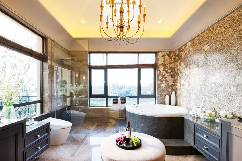 Modern bathroom with large round tub, dark vanity, outdoor views and chandelier
