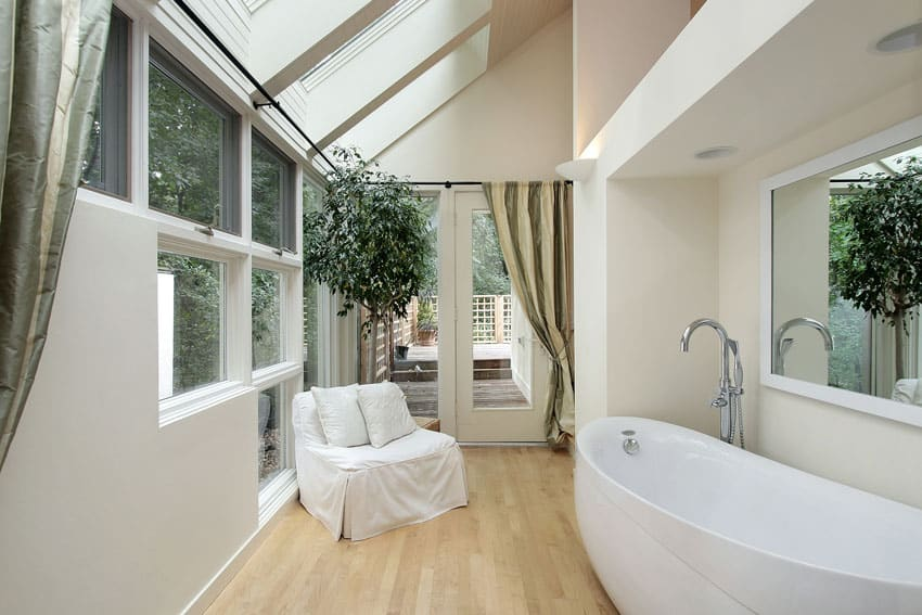 Modern bathroom with wood floors, large windows and lounge chair