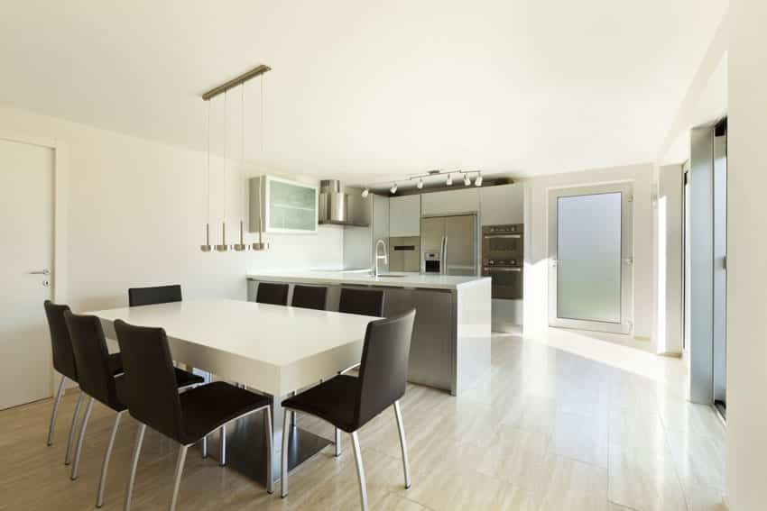 Modern dining table in open kitchen with white table, black chairs and chrome pendant lights