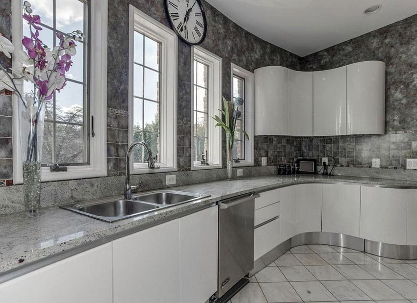 Modern kitchen with andino white granite counters, white cabinets and gray backsplash tile