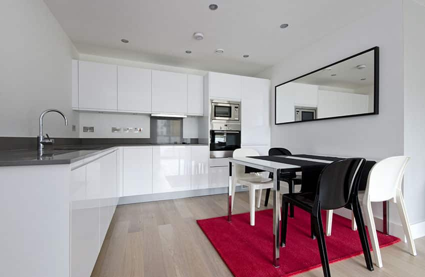 Modern kitchen with black counter and white cabinets with l shape design