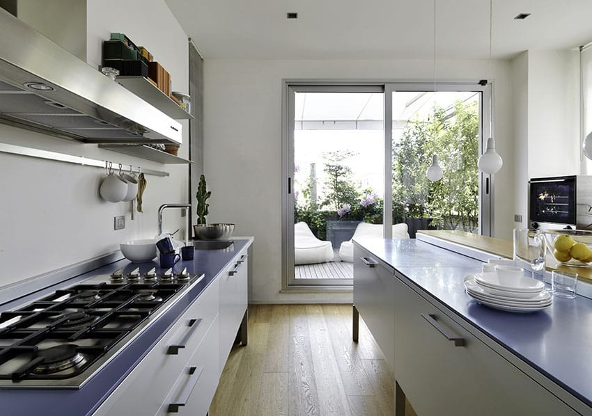 Modern kitchen with blue counters, white cabinets and wood flooring