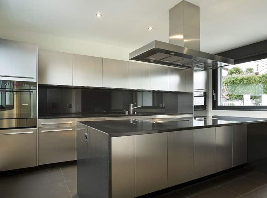 Modern kitchen with white cabinets, dark gray countertop and backsplash