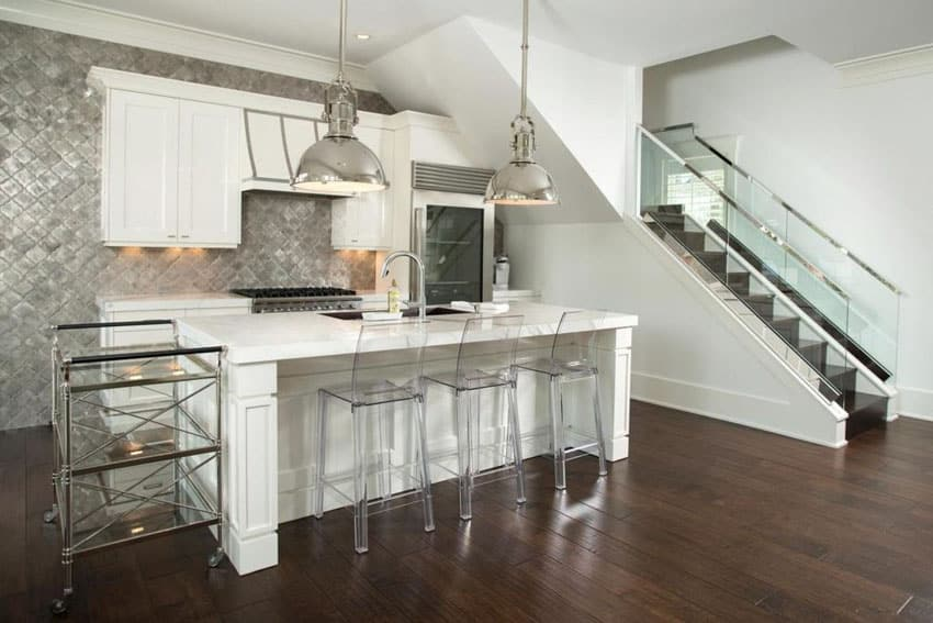 Modern kitchen with white cabinets, metal backsplash, engineered hardwood floors, and chrome pendant lights