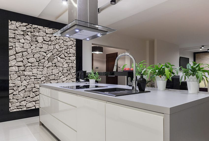 Modern kitchen with white island and stacked stone accent wall