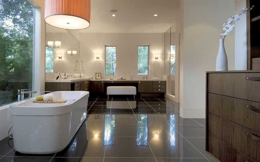 Modern master bathroom with freestanding tub black, granite floors and white vanity counters