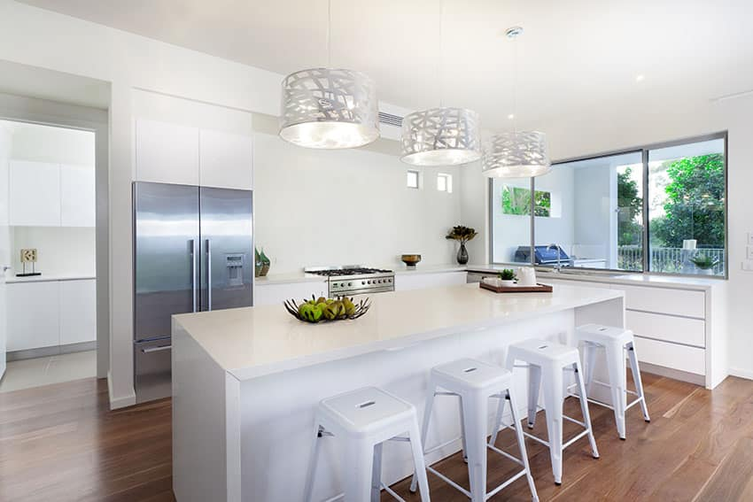 Modern white cabinet kitchen with island with simple bar stools and silver drum pendant lights