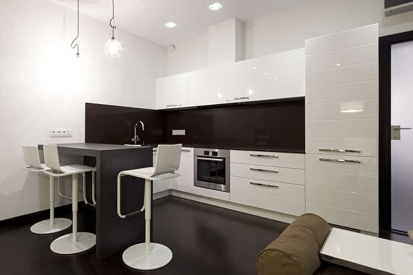 Modern white kitchen with small breakfast bar peninsula and brown glass backsplash