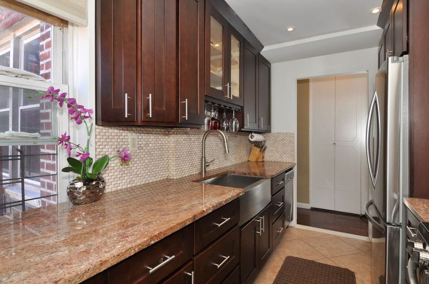 Narrow galley kitchen with brown cabinets and red astoria granite counter