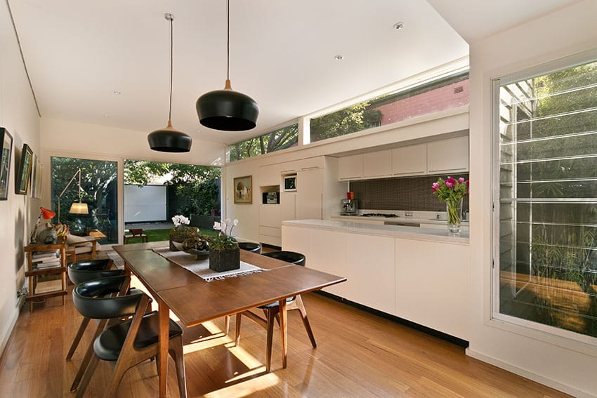 Natural light white modern kitchen with wood dining table and wood flooring