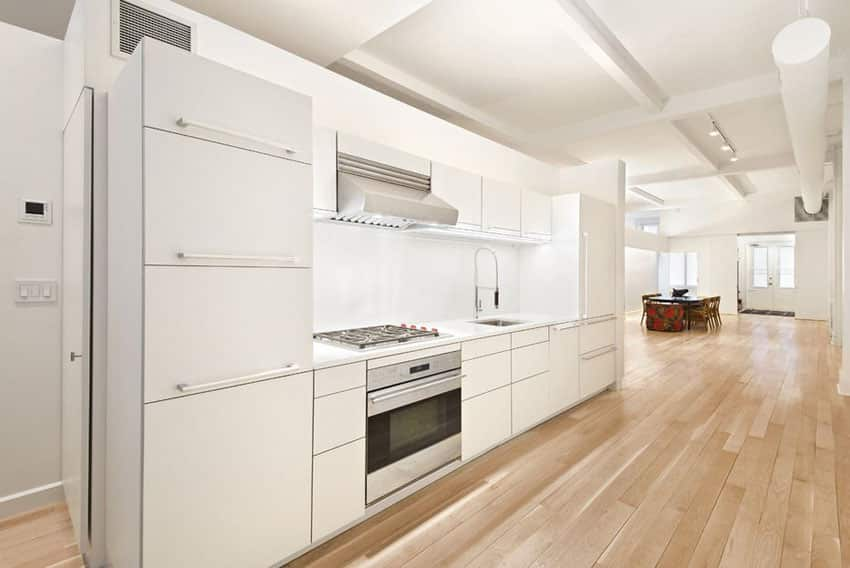 One wall modern kitchen with white cabinets and birch wood floors