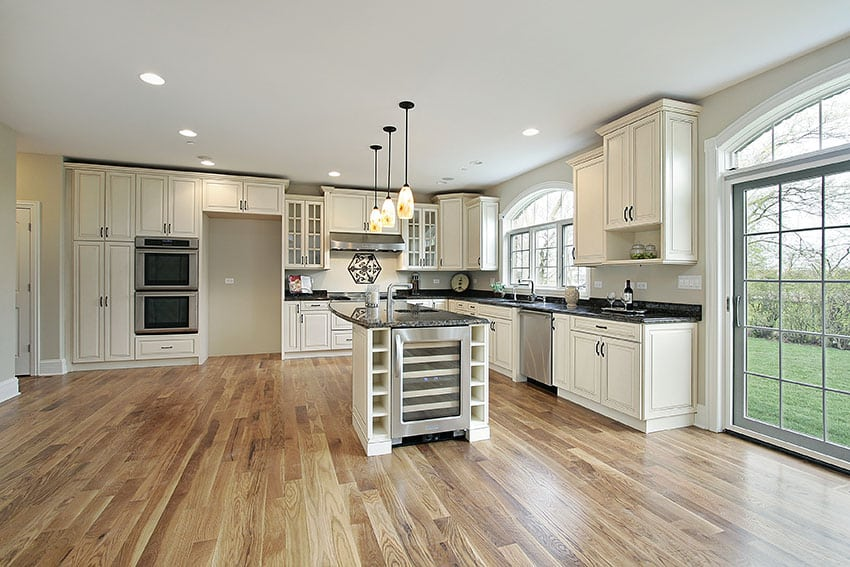 Open plan kitchen with antique cabinets, wood floors and french doors