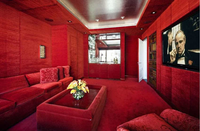 Plush red velvet movie room with wide screen television and home bar