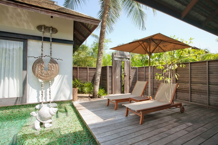Asian style backyard with horizontal wood fence and lounge deck next to pool