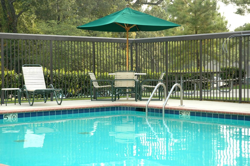 Peaceful poolside scene, with umbrella, table and chairs