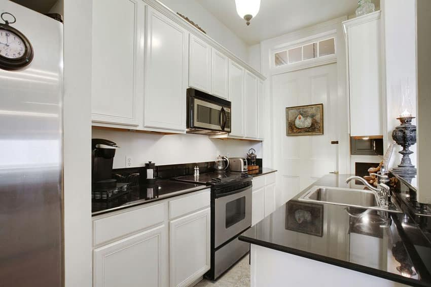 Small black and white galley kitchen with traditional white raised panel cabinets and black counters