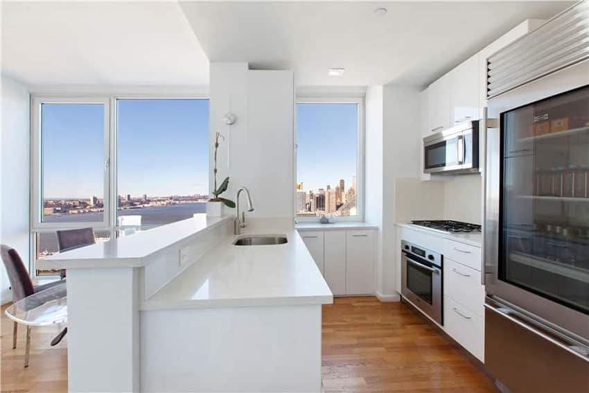 Small contemporary white galley kitchen with white countertops and cabinets with glass door refrigerator
