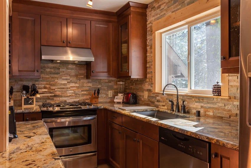 Small craftsman galley kitchen with stacked stone backsplash, brown cabinets and beige granite countertops