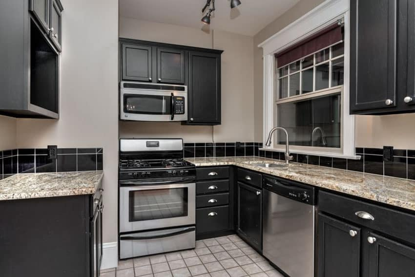 Small galley kitchen with black cabinets and avalon white granite