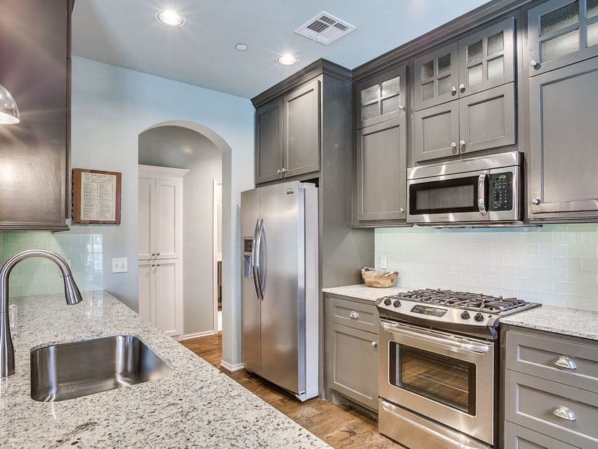 Small galley kitchen with gray cabinets, andino white granite and light blue subway tile backsplash