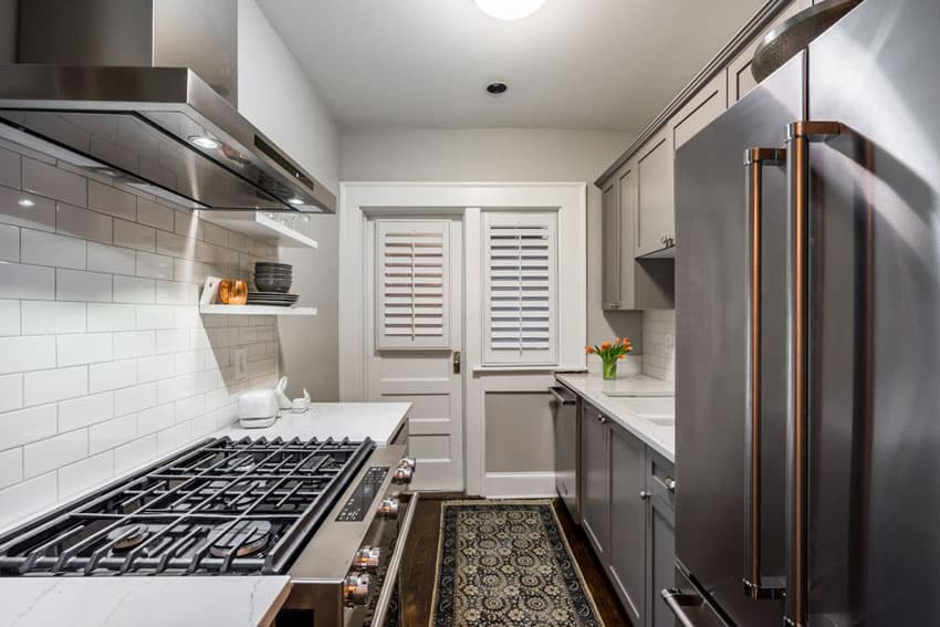 Small galley kitchen with gray cabinets, white marble counters and hardwood flooring