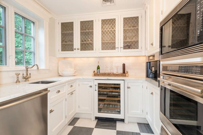 Small galley kitchen with white cabinets with glass pane doors, carrara marble counter and black and white checkered floors