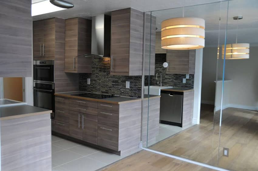Small modern galley kitchen with brown textured laminate cabinets and gray porcelain tile floors