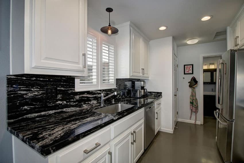 Small traditional galley kitchen with white raised panel cabinets and black space granite counter
