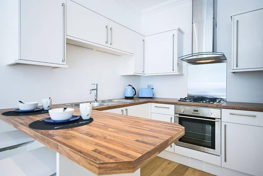 Small white modern kitchen with wood counter peninsula