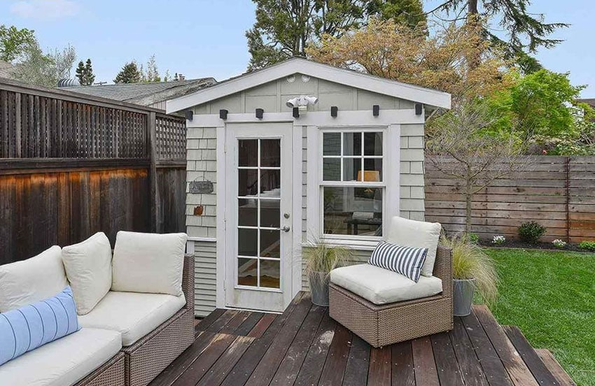 Small wood shed in backyard with deck and lounge chairs