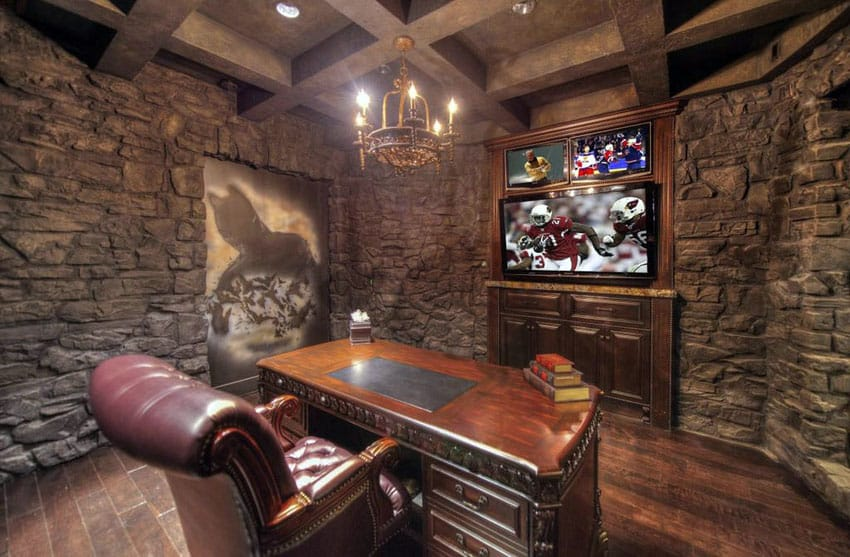 Stone wall man cave office with desk, wood flooring and big screen television
