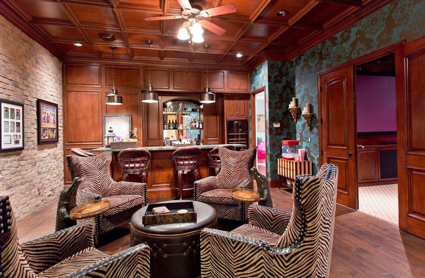 Swanky man cave bar with patterned chairs and door to movie room