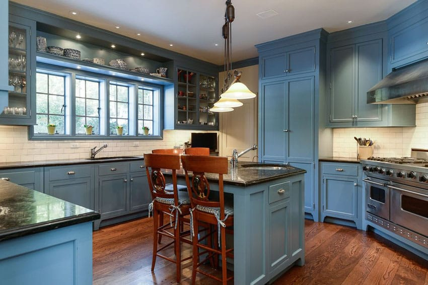 Traditional kitchen with light blue cabinets, white subway tile and dark oak hardwood flooring