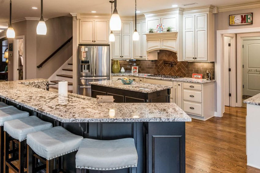 Traditional kitchen with long breakfast bar island, off white cabinets and wood flooring
