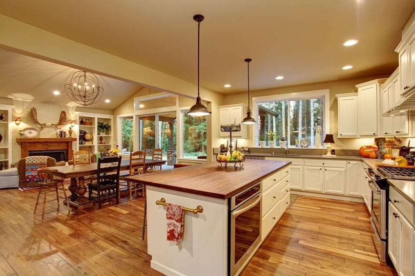 Traditional kitchen with white cabinetry butcher block island with wood plank flooring