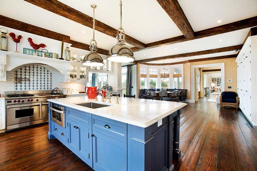 Traditional kitchen with white cabinets and blue island with exposed beam ceiling and open layout
