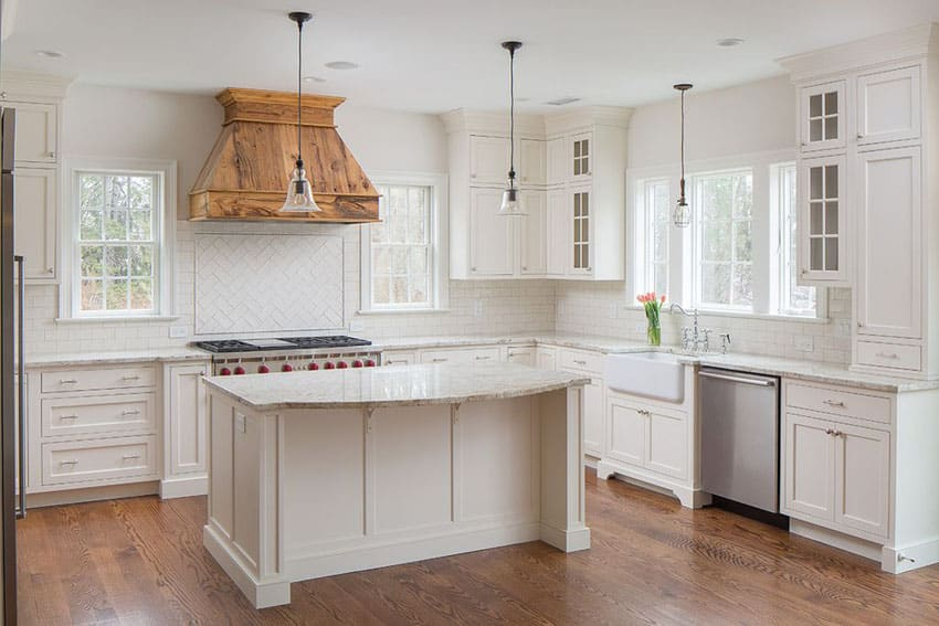 Traditional kitchen with white cabinets, calacatta carrara marble counter, farmhouse sink and subway tile
