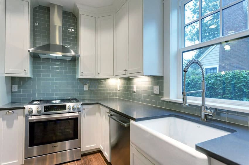 Traditional kitchen with white cabinets, concerto quartz counters and blue subway tile backsplash