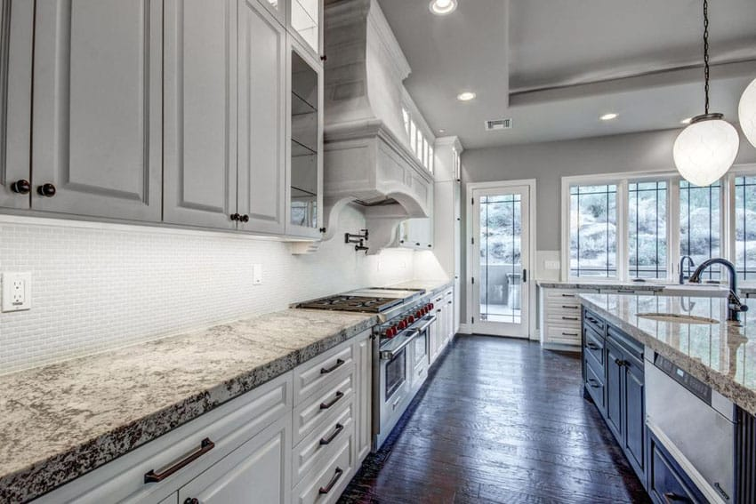 Traditional kitchen with white lower cabinets and gray upper cabinets with blackened hickory floors